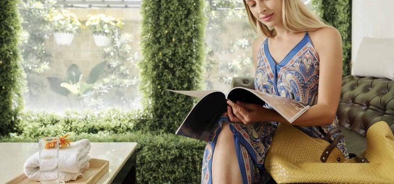 Cheerful woman reading magazine
